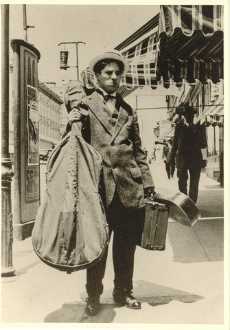 Chaplin carrying his cello and violin on tour with Karno