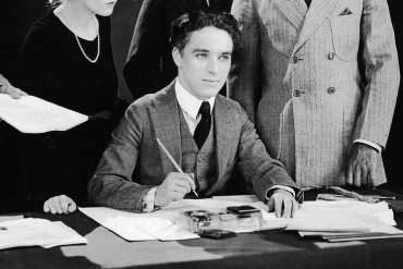 Chaplin signing the articles for United Artists